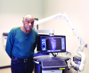 Charles Jones stands with the LUNA system, which helped with the treatment of his diabetic foot ulcer.