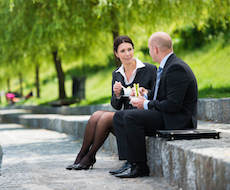 Two business colleagues having a conversation while having a lunch break on the embankment in a park.